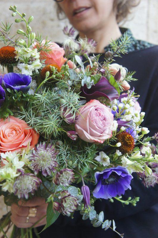 portrait d'aurore, gérante de fleurine, tenant un bouquet